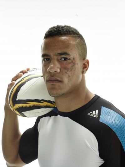 Portrait of Anthony Watson looking at an angle to the camera holding a rugby ball to his shoulder
