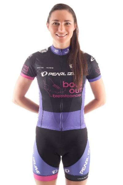 Shot of Dame Sarah Storey in her racing uniform stood up smiling at the camera with her arms behind her back