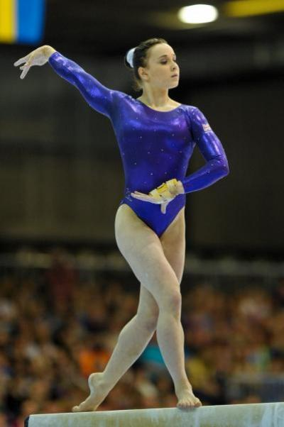 Shot of Hannah Whelan on a balance beam posing with her right hand in the air