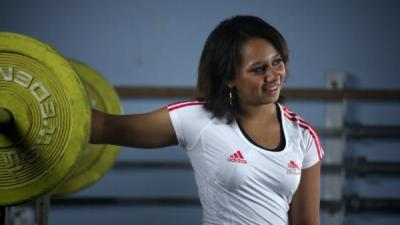 Image of Zoe Smith looking away from the camera with her right arm resting backwards on a set of weights