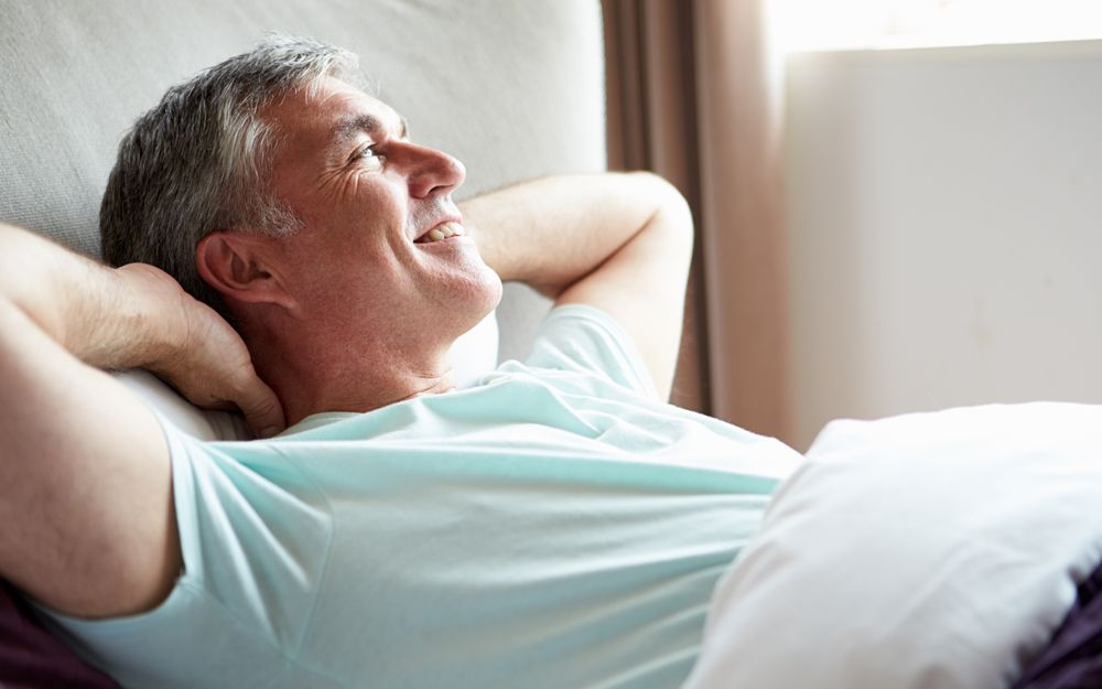 A man lying back in bed, happy and without a bad back thanks to the support of a comfortable orthopaedic mattress