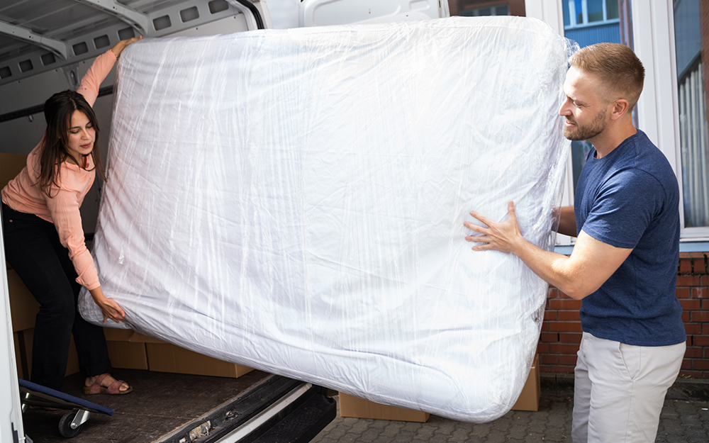 Couple lifting a mattress out of a van
