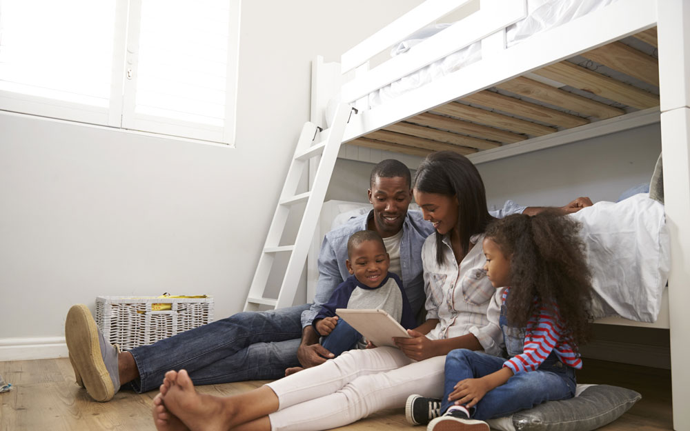 Family reading a story near to the bunk bed