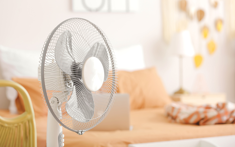 A fan pointing at a bed