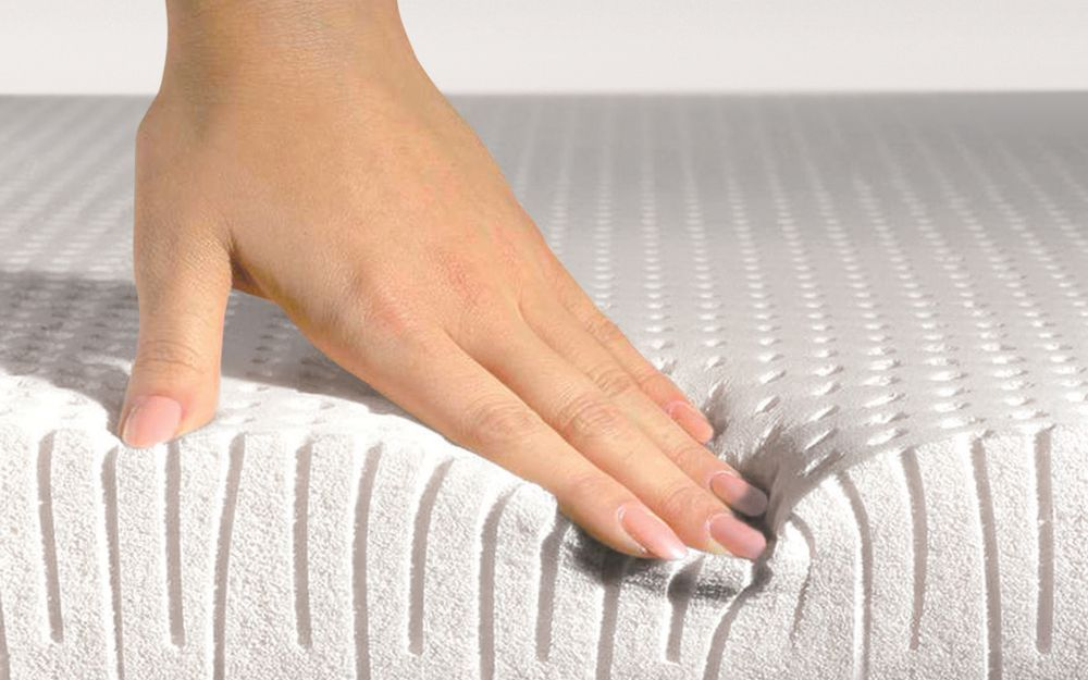 Hand presses on a latex foam mattress