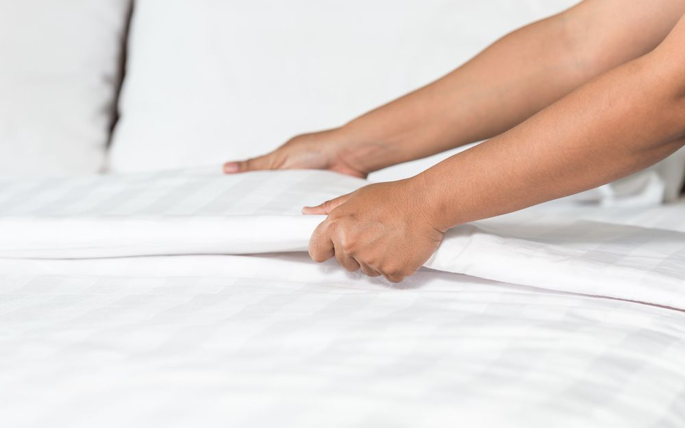 A person putting bed sheets back on the bed