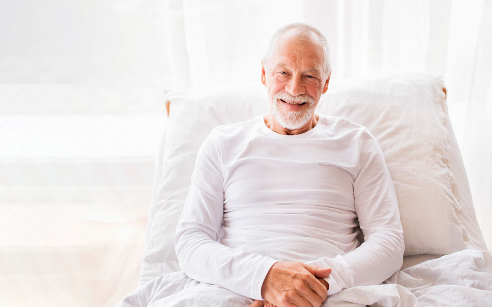 Elderly man sitting up in adjustable bed
