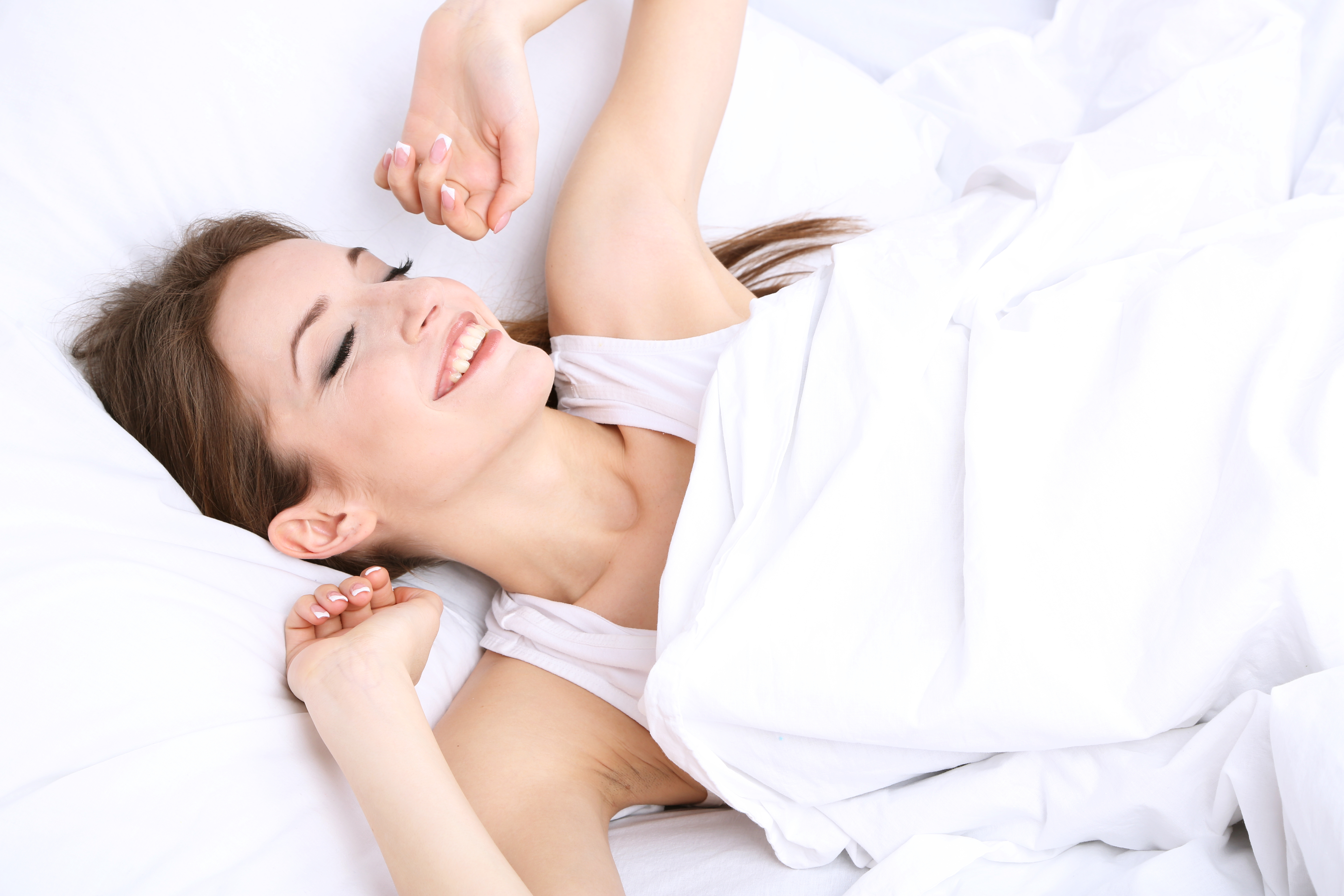 Woman waking up refreshed without back pain thanks to the comfort and support of an orthopaedic mattress
