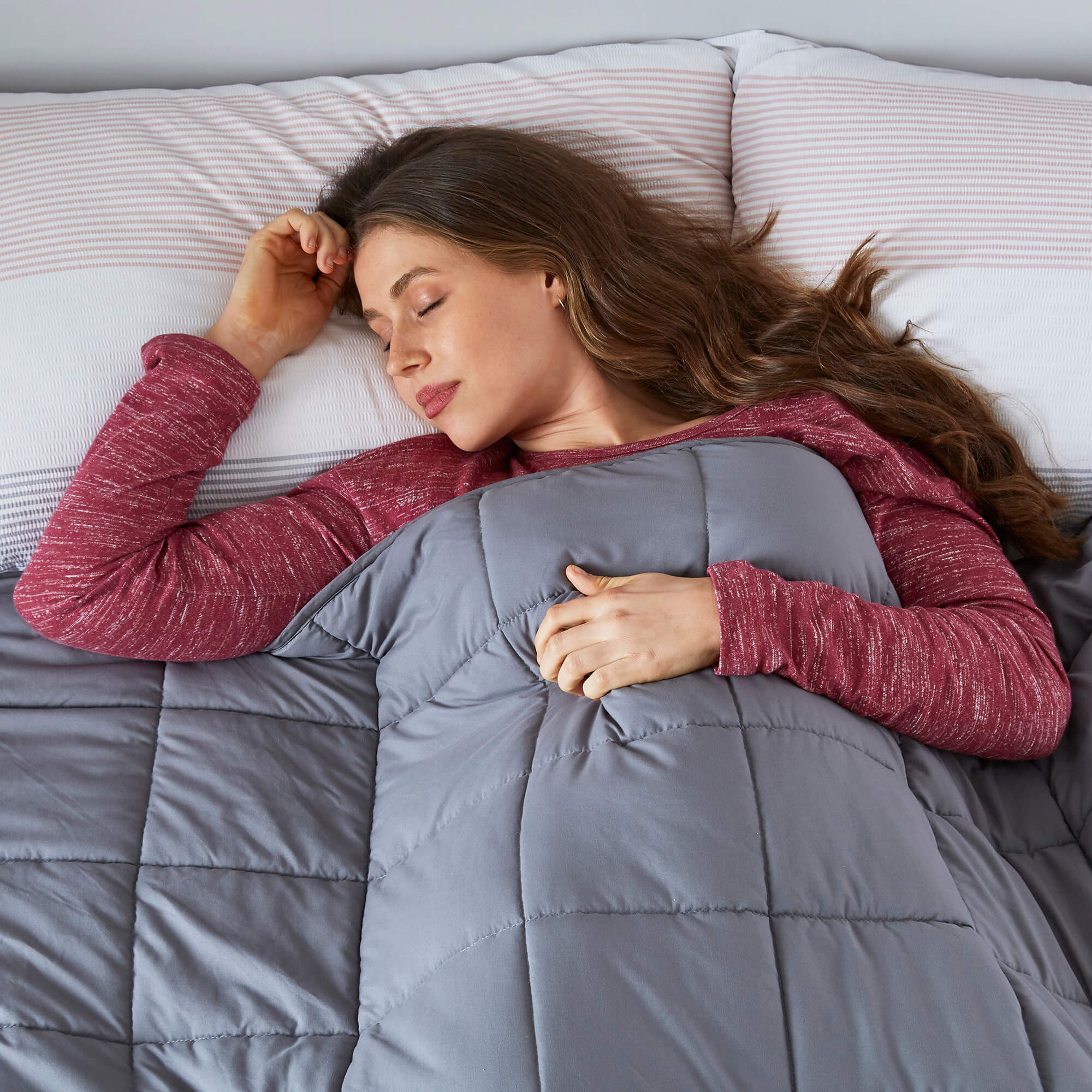 A woman sleeping under a weighted blanket