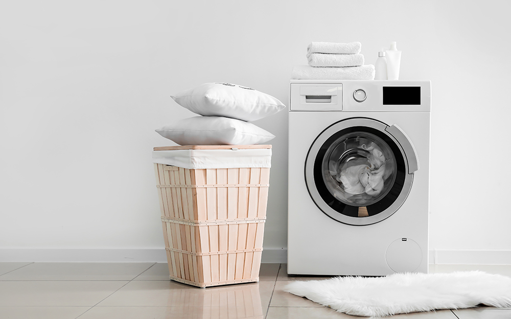 A washing machine with a pile of pillows