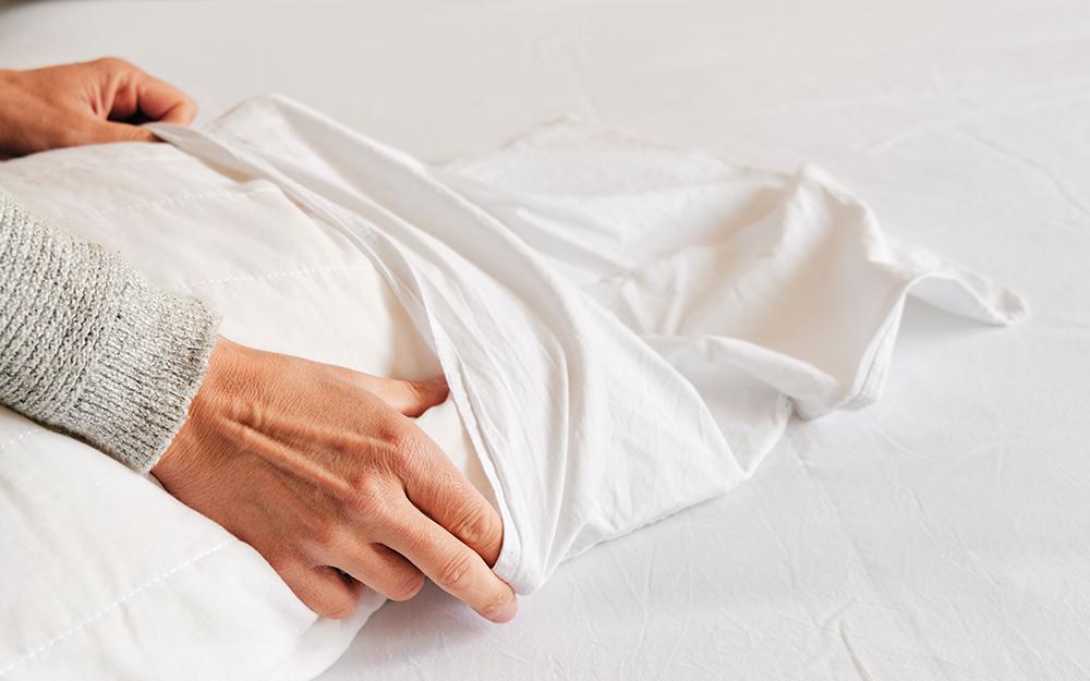 A woman putting a pillowcase over a pillow