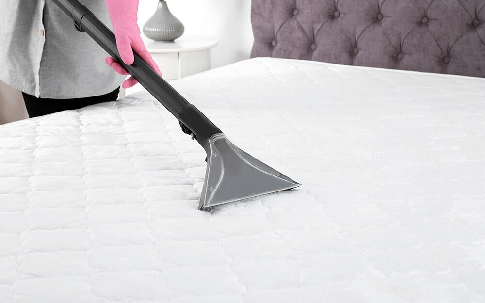 A woman vacuuming a mattress