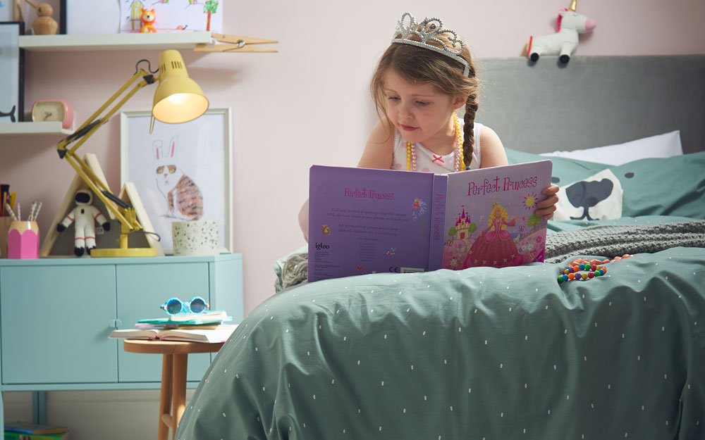 Child reading in her own bed