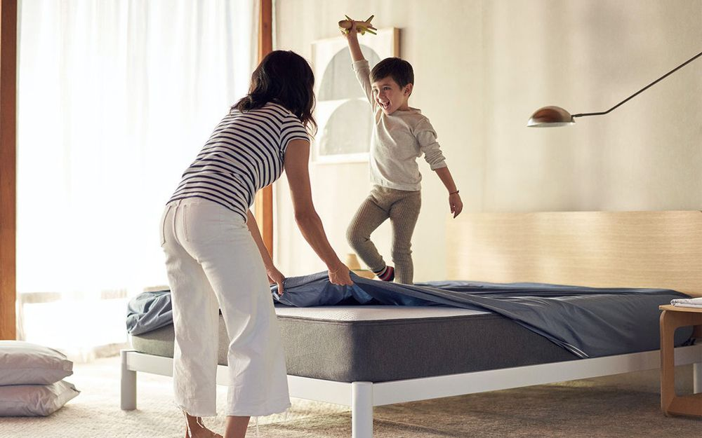 Woman removing bedding from mattress
