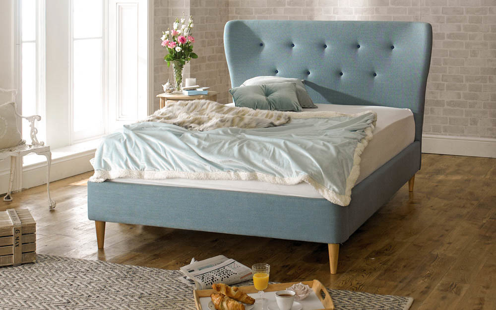 The Limelight Aurora Fabric Bed Frame features a high, winged headboard and stylish tapered legs