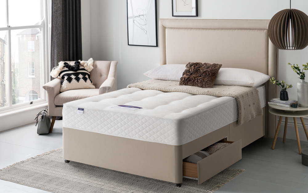 The platform base Silentnight Ortho Dream Star Miracoil Divan Bed in a bedroom with two drawers open