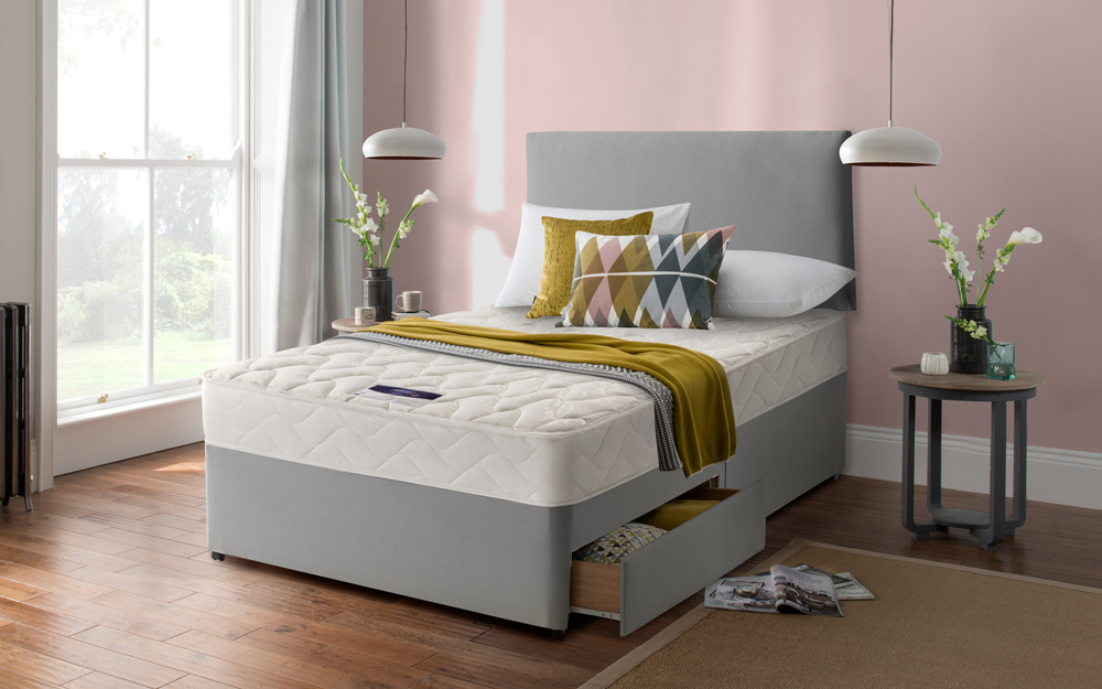 The Silentnight Vilana Limited Edition Miracoil Divan Bed in a bedroom with two drawers