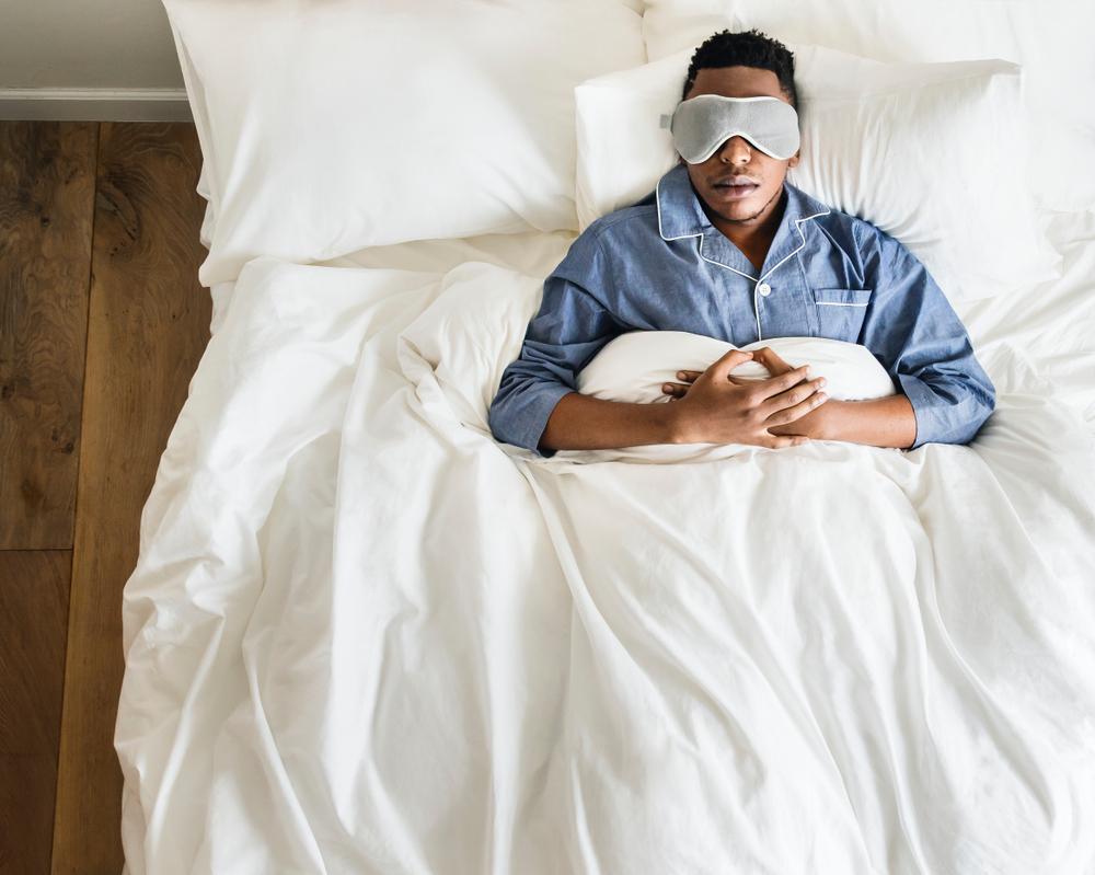 Man asleep in bed with eyemask wearing pyjamas