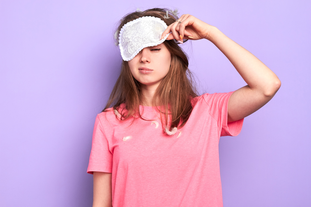 Tired woman in pink t-shirt and eyemask