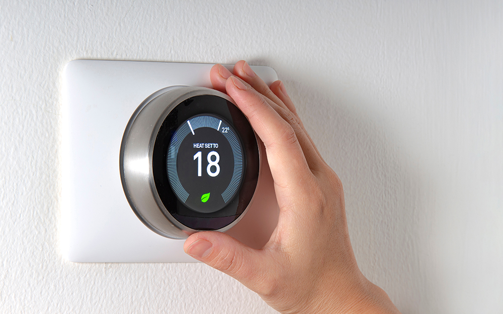 Person changing thermostat temperature to 18 degrees celsius
