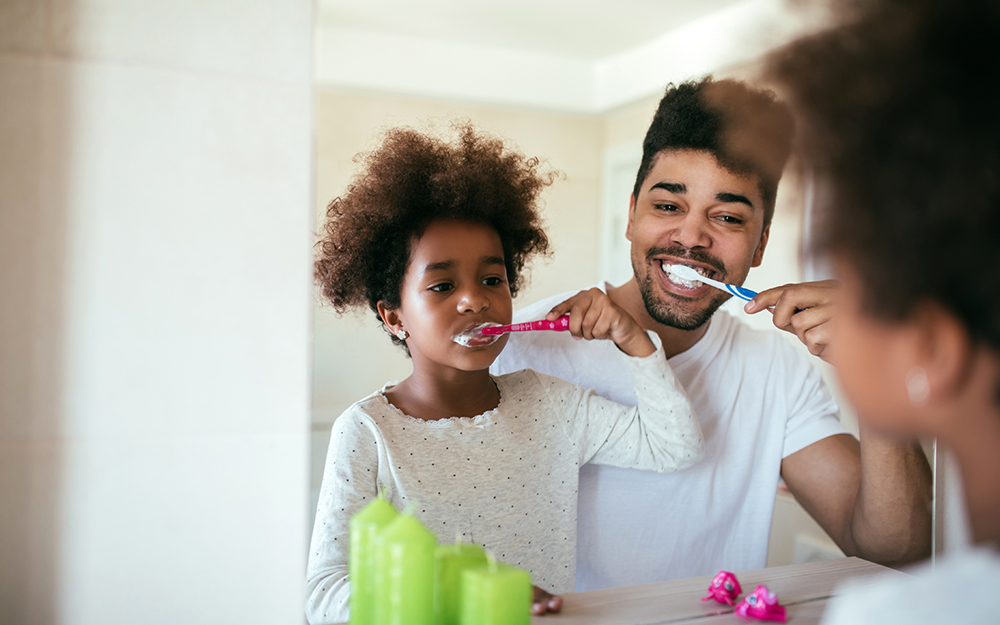 Dad and daughter brushing teeth before bed