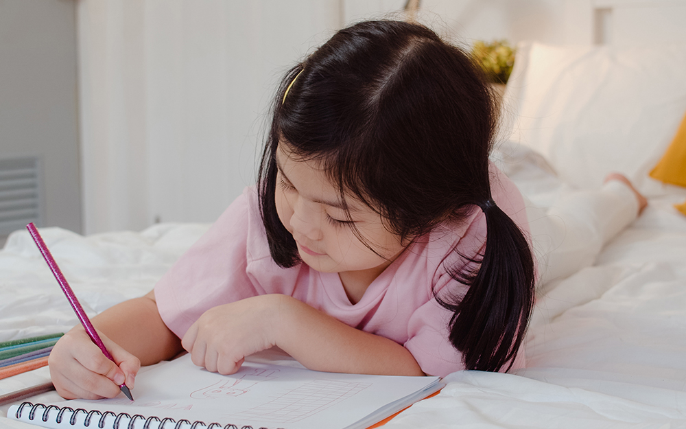 Young girl drawing in bed