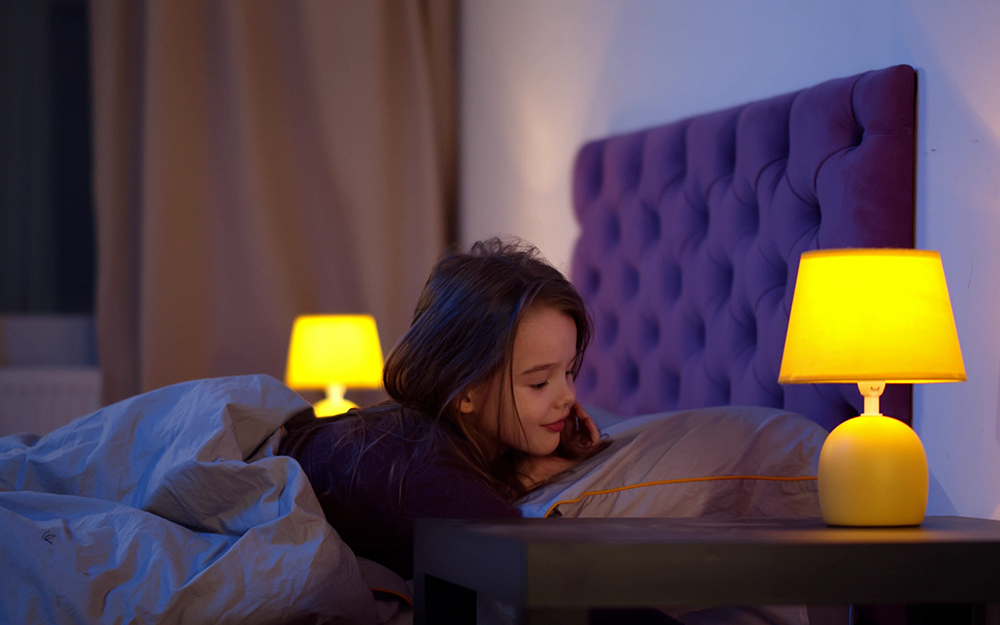 Girl in bed waking up with a lamp