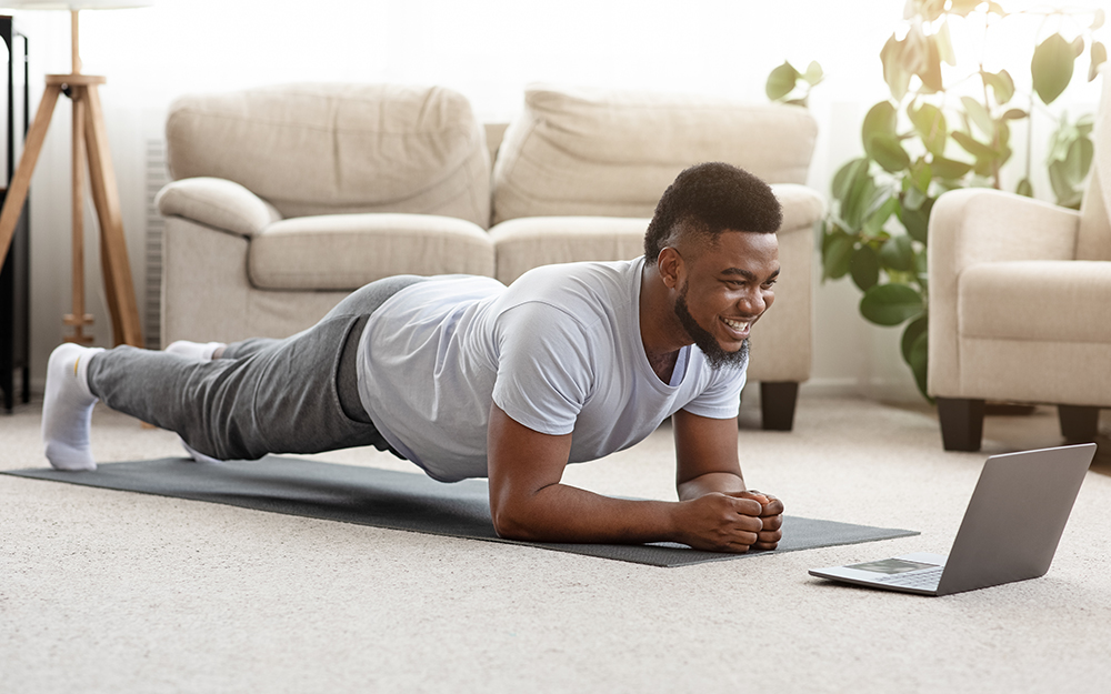 Man exercising in front of laptop