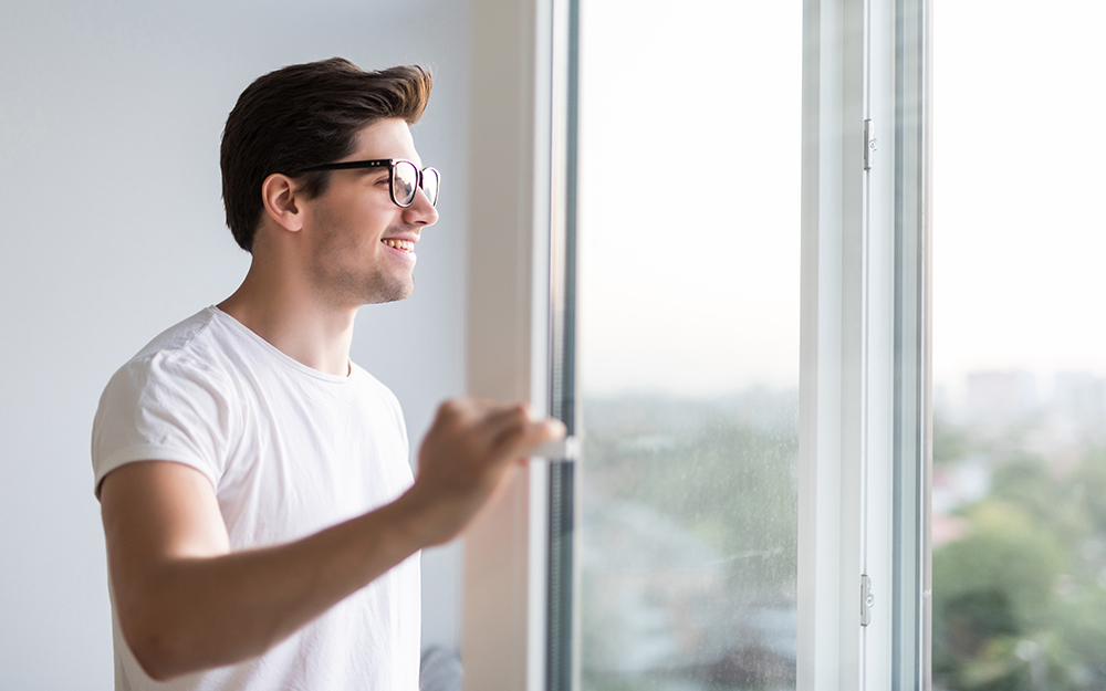 Man opening window in the morning