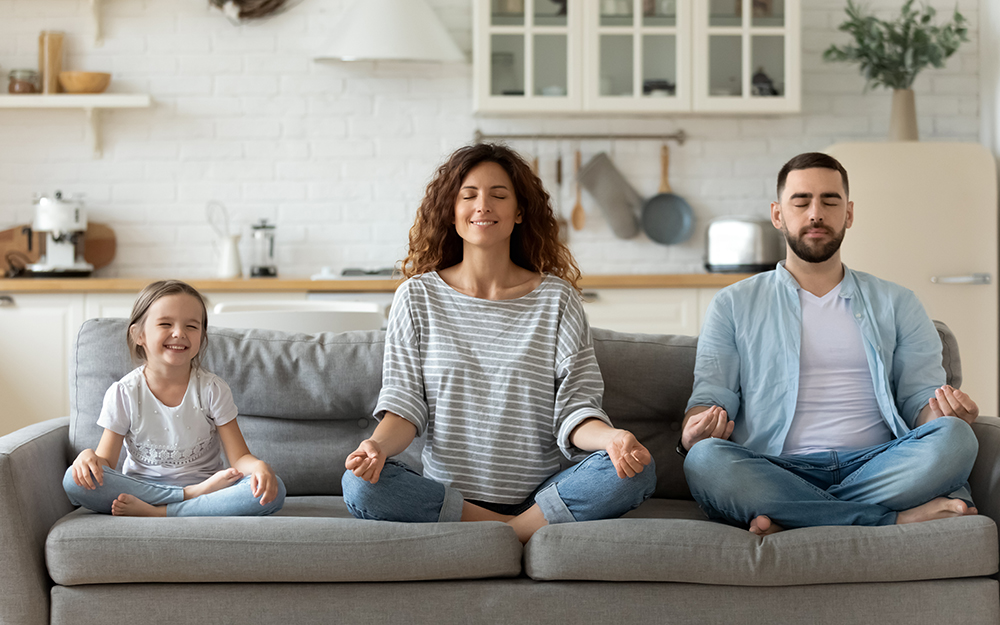 A family sitting on the sofa and meditating
