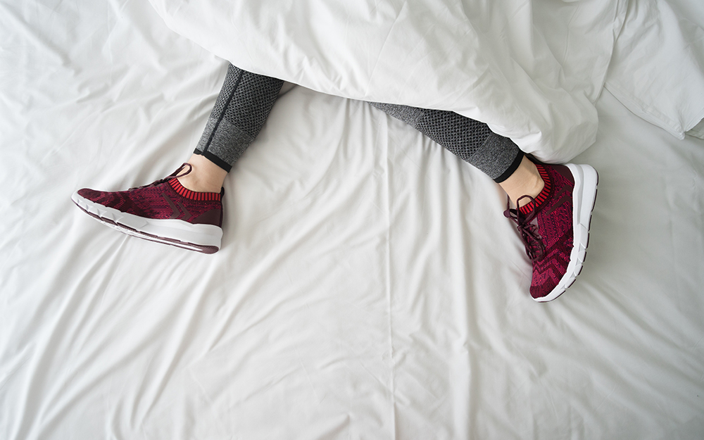 Someone sleeping with trainers on in bed