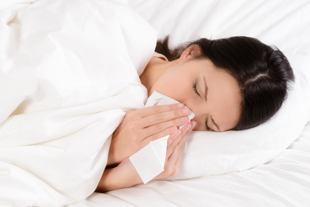 Woman sneezing into tissue in bed