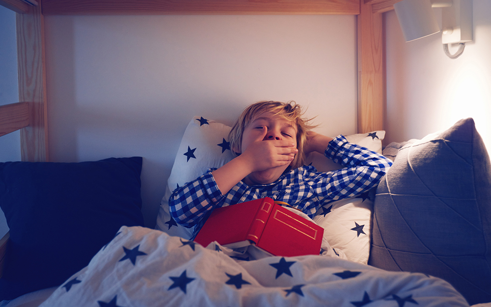 Young boy yawning in bed