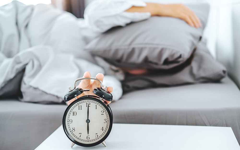 Person in bed trying not to look at alarm clock