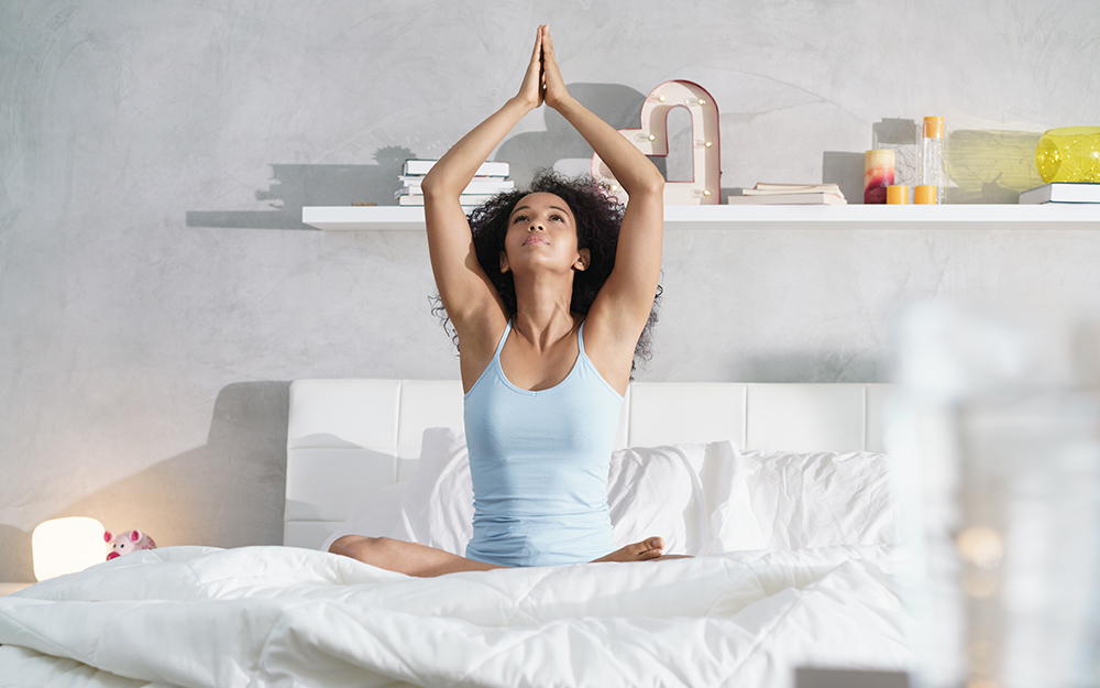 A woman doing yoga on her bed