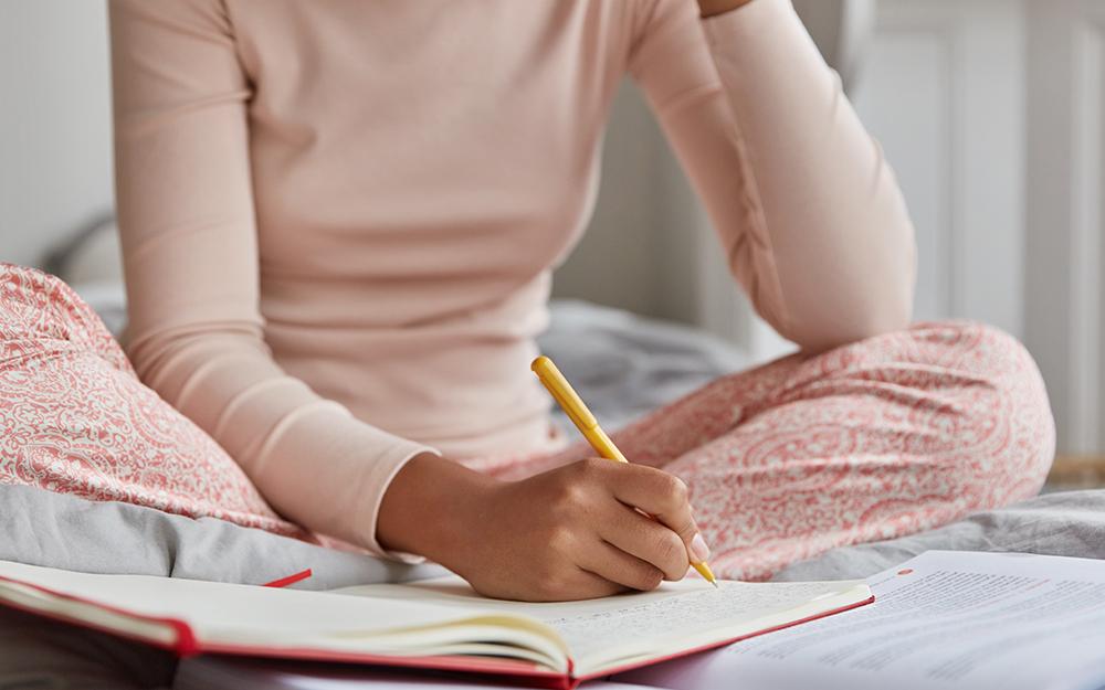 A woman in pyjamas writing in her sleep diary