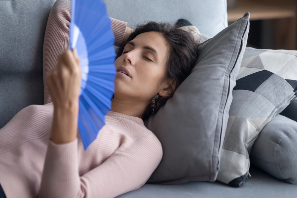 Woman trying to sleep on sofa cushion with blue fan