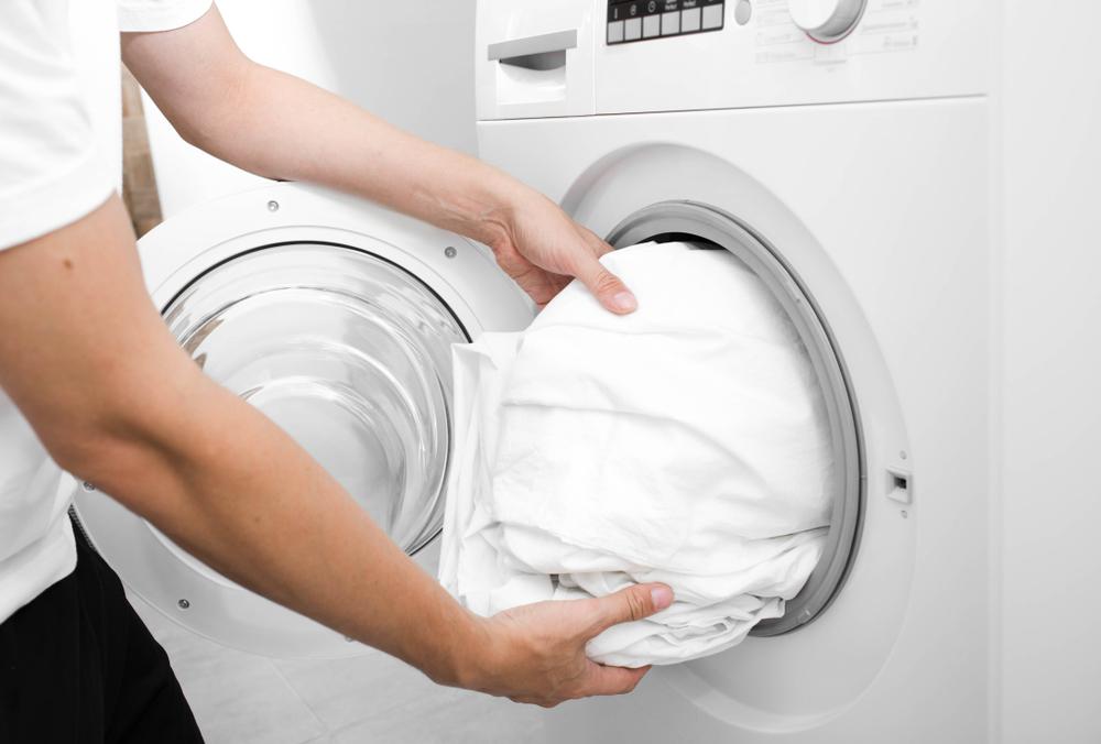 Person putting white bedding into washing machine