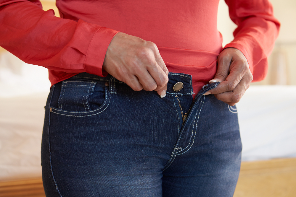 Woman trying to fasten tight jeans