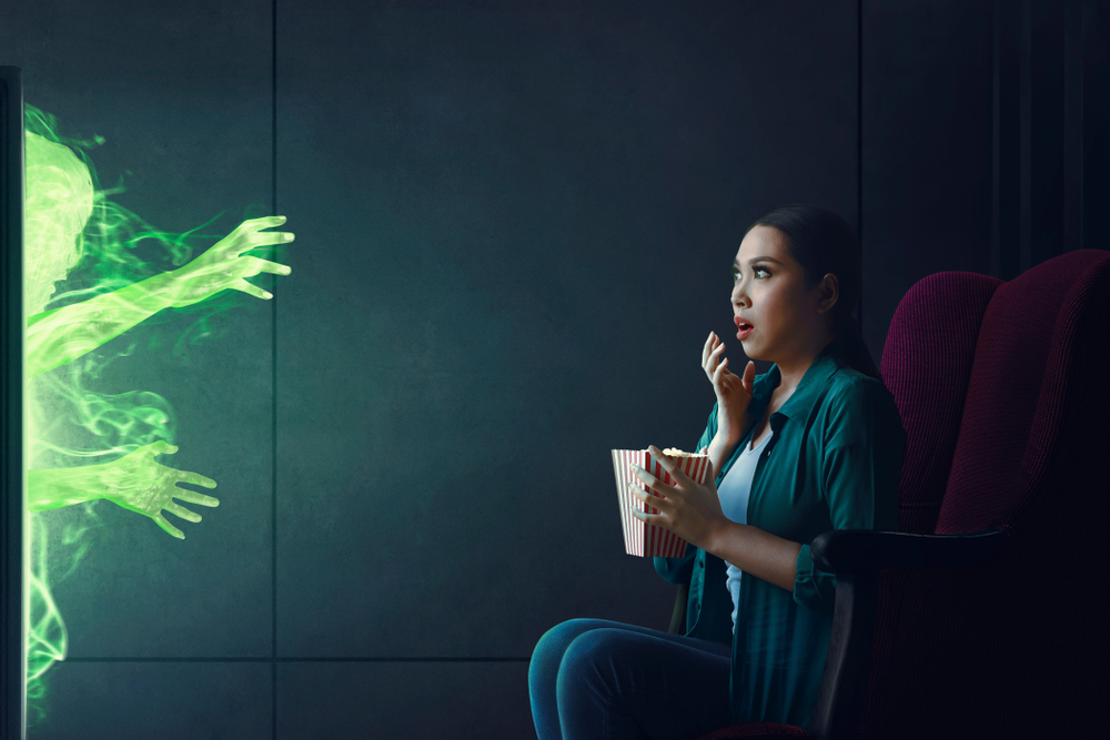 Woman looking scared watching horror film with green ghost coming from the television