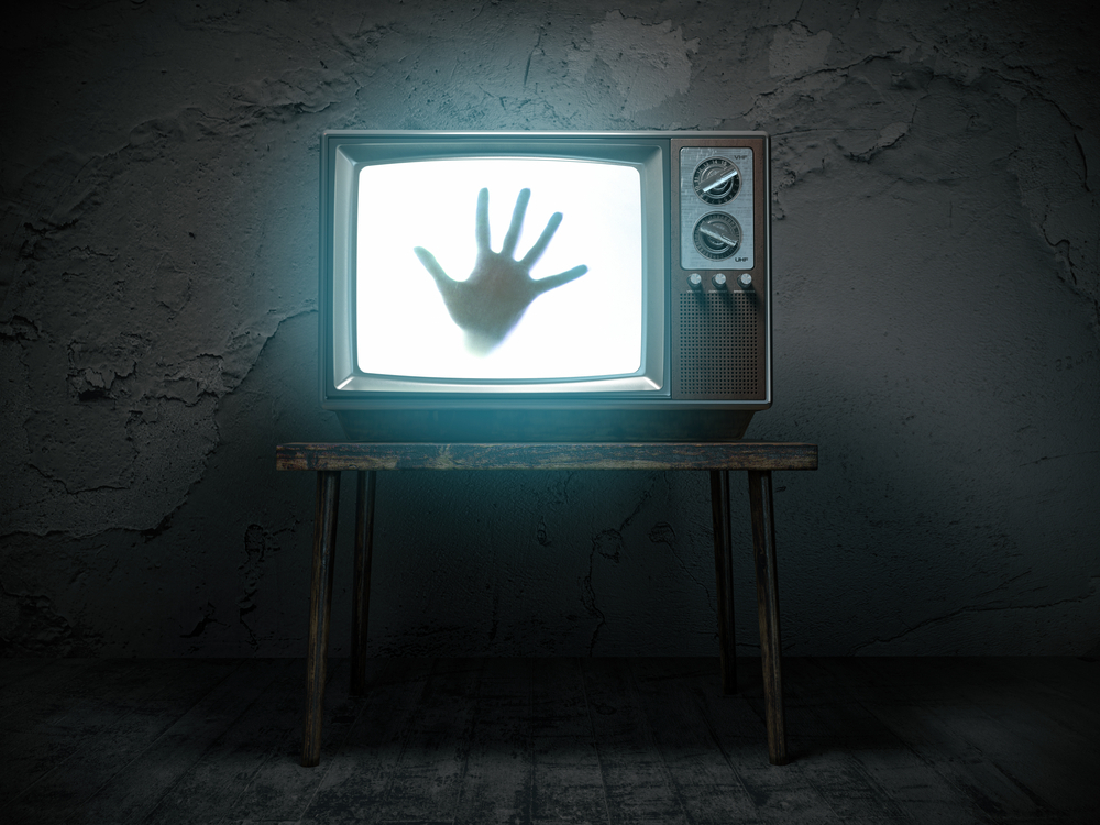 Dirty room with old television playing horror movie showing hand reaching out